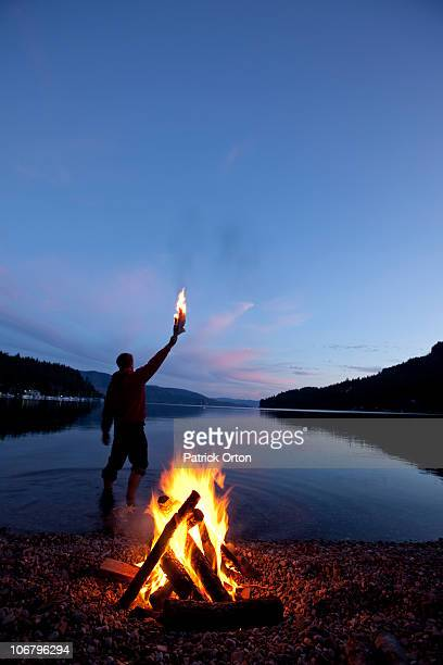 Lone figure stands behind campfire in Idaho.
