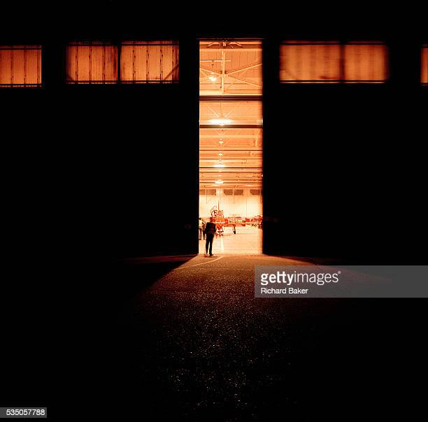 A lone figure stands silhouetted against a hangar belonging to the elite 'Red Arrows' Britain's prestigious Royal Air Force aerobatic team at RAF...