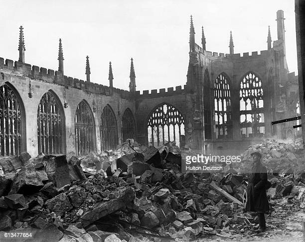 A lone figure stands surrounded by rubble amid the ruins of Coventry Cathedral devasted during a German bombing raid England November 1940