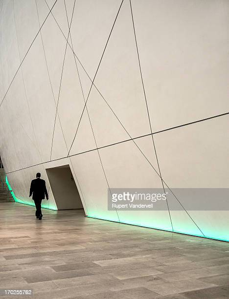 Lone figure walks against very high geometric wall and doorway. The location is the Natural History Museum, London. This is an example of isolation,...