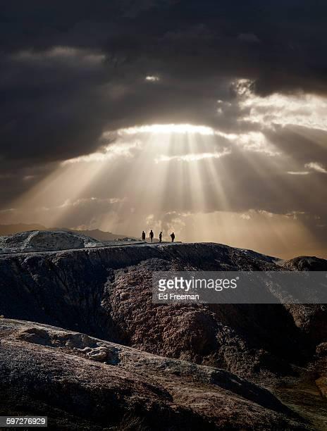 lone figures, mountain, dramatic sky - sonnenstrahl stock-fotos und bilder