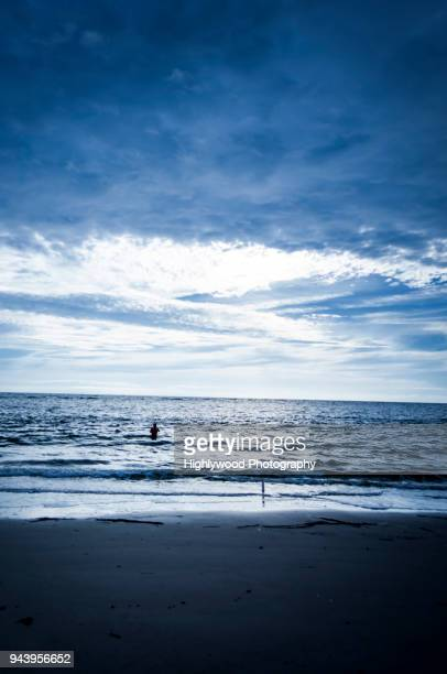 lone fisherman in the ocean - highlywood stock pictures, royalty-free photos & images