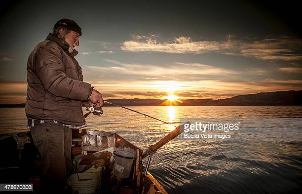 Lone fisherman on a boat at sunrise