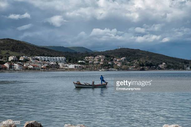 lone fisherman on his small boat near the shore . - emreturanphoto stock pictures, royalty-free photos & images