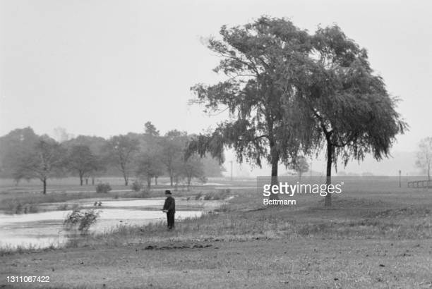 Lone fisherman standing in the rain on the bank of the Flushing River in Flushing Meadows in the Queens borough of New York City, New York, 23rd...