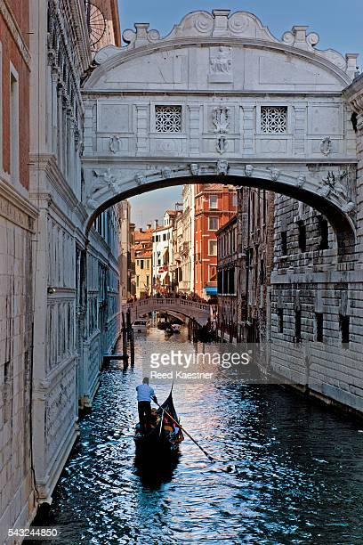 A lone gondola passes under the Bridge of Sighs at sunset, Venice, Italy