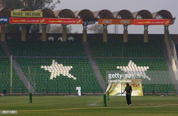 Lone ground keeper waters the pitch as the Gaddafi Stadium stands empty on March 4, 2009 in Lahore, Pakistan. Lahore recovers from Tuesday's...