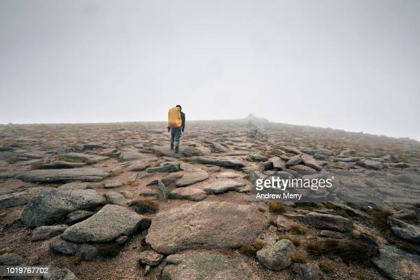 lone hiker, mountain climber appraoching the summit of cairn gorm mountain, cairngorms, scotland - extreme terrain stock pictures, royalty-free photos & images