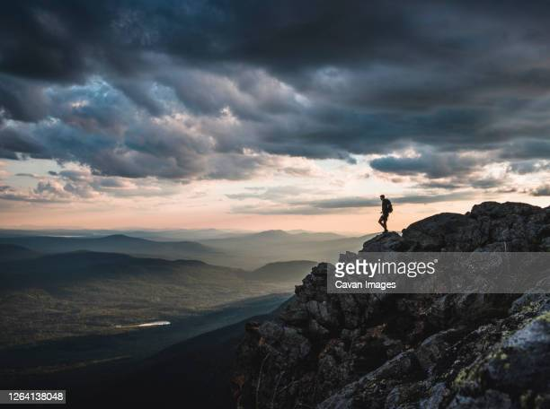 lone hiker on mountain summit appalachian trail at sunset, maine. - appalachian trail stock pictures, royalty-free photos & images
