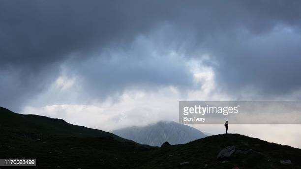 lone hiker silhouetted against dramatic sky and mountains in snowdonia - mountain ridge stock pictures, royalty-free photos & images