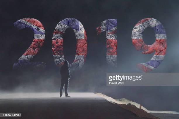 a lone hooded figure looking at a cracked, ruined 2019 new year logo on a dark, misty, scary night. - 2019 stock pictures, royalty-free photos & images