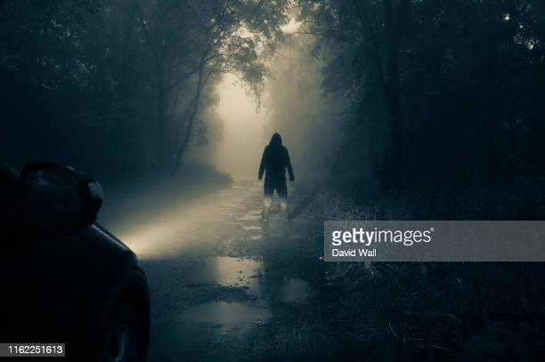 a lone, hooded figure standing in front of a car looking at an empty misty country road silhouetted at night by car headlights - horror stock pictures, royalty-free photos & images