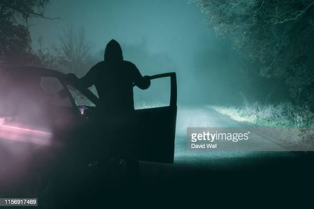 a lone, hooded figure standing next to a car looking at an empty misty winter country road silhouetted at night by car headlights - crimine foto e immagini stock