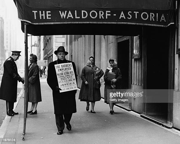 Lone hotel barber, a member of the AFL-CIO, carries a sign objecting to scab employees as he strikes outside the Waldorf-Astoria Hotel, New York...