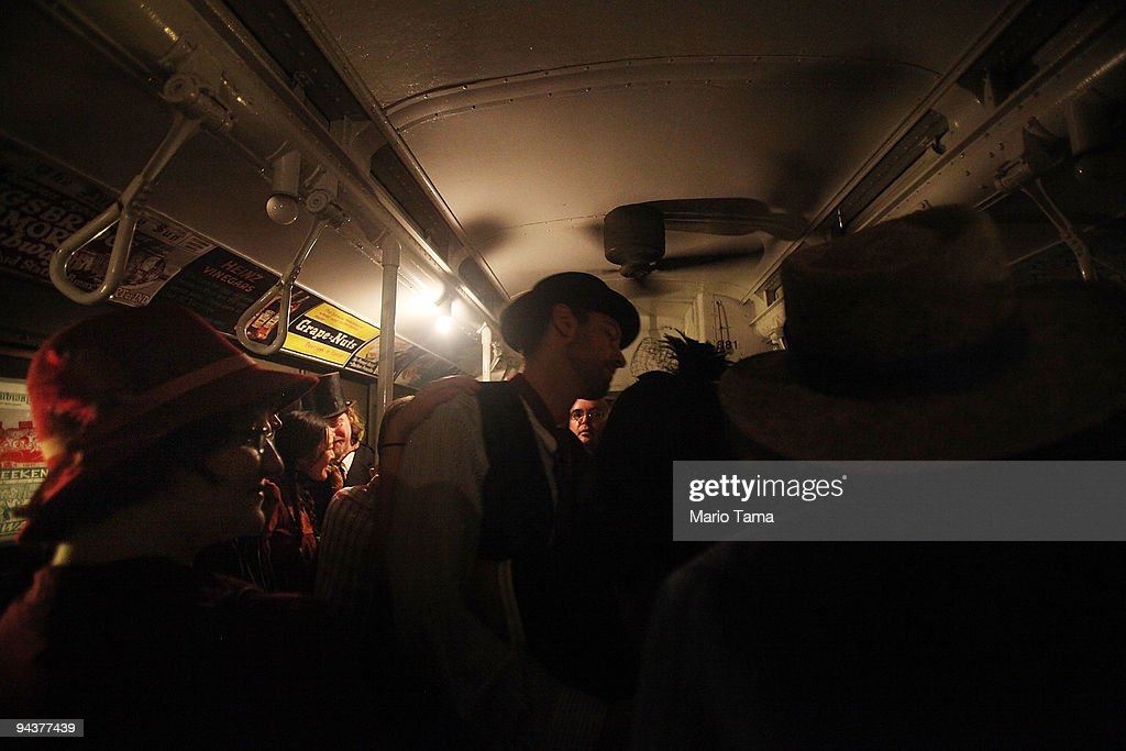 A lone incandescent bulb is all that illuminates costumed revelers riding after other bulbs briefly went out on an antique subway train during a 'Vintage Tea Party' hosted by Levy's Unique New York tour group December 13, 2009 in New York City. New York City Transit is running a special subway train with cars in service from the 1930's-1970's every Sunday this month from Manhattan to Queens complete with ceiling fans and wicker seats.