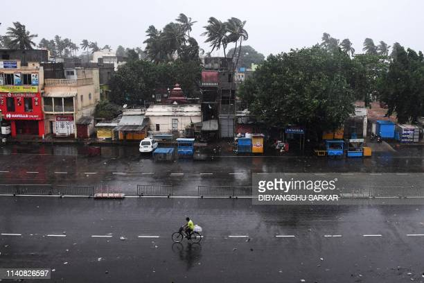 TOPSHOT A lone Indian commuter cycles down nearly deserted road in Puri in the eastern Indian state of Odisha early on May 3 as Cyclone Fani...