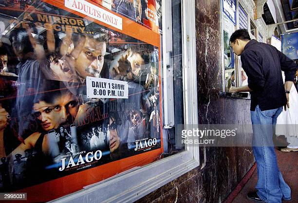 """Lone Indian movie goer purchases a ticket at Metro cinema in Bombay, 18 February 2004, where the latest movie """"JAAGO"""" is screening. The movie,..."""