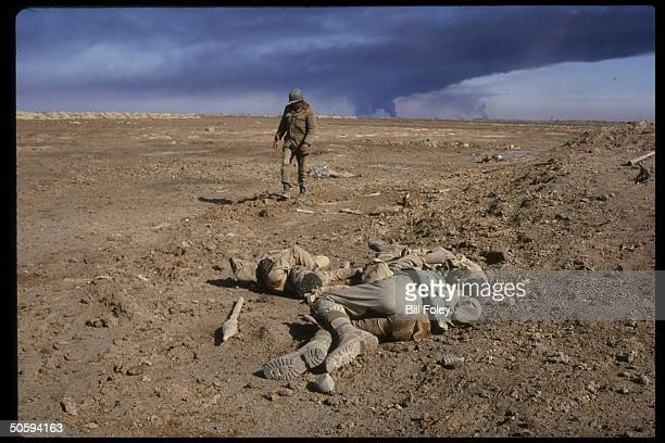 Lone Iraqi soldier walking past group of corpses of Iranian soldiers killed in battle during IranIraq war in desolate landscape