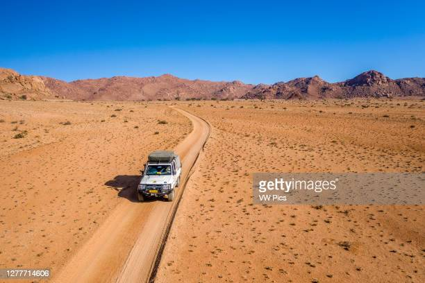Lone jeep on an expedition across the desert , Helmeringhausen, Namibia.