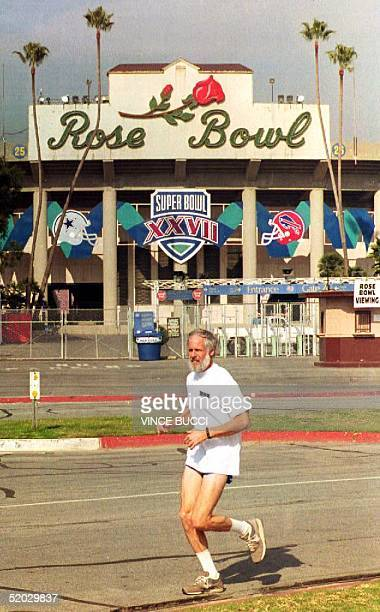 A lone jogger passes in front of the Rose Bowl 28 January 1993 as preparations continue for Super Bowl XXVII In Los Angeles CA The Dallas Cowboys...