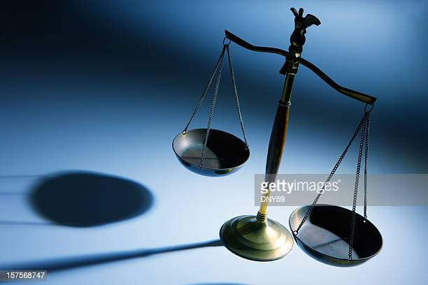 lone justice scale on simple blue background - equal arm balance stock pictures, royalty-free photos & images