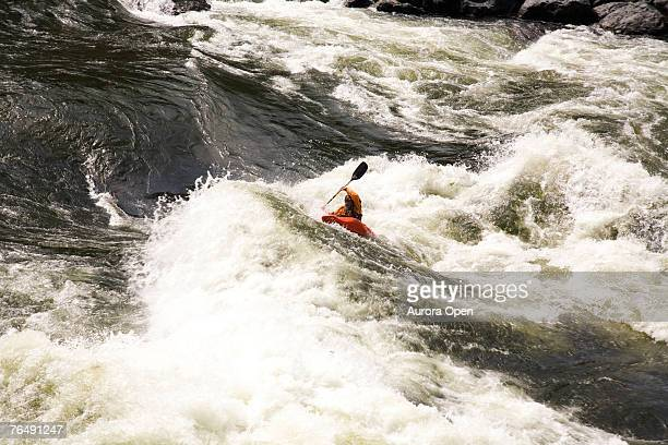 A lone kayaker fights through large rapids on the Snake River in Oregon.