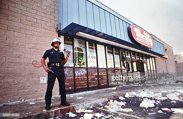 A lone LAPD officer keeps looters at bay from a Thrifty Drug and Discount store Most of the store was cleaned out by looters Los Angeles has...
