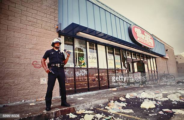 A lone LAPD officer stands guard outside a Thrifty Drug Store in South Central LA Los Angeles has undergone several days of rioting due to the...