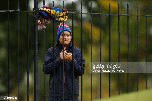 A lone Lions fan cheers from outside the ground after all fans have been locked out due to the coronavirus pandemic during the AFLW Semi Final match...