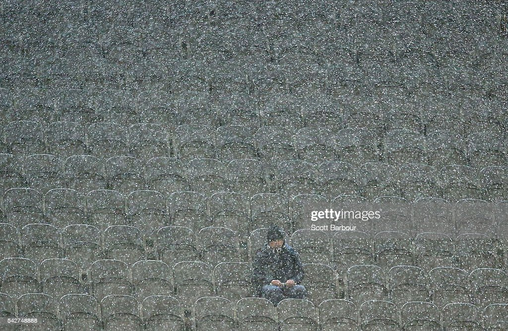 A lone Magpies supporter in the crowd looks on as it rains during the round 14 AFL match between the Collingwood Magpies and the Fremantle Dockers at Melbourne Cricket Ground on June 24, 2016 in Melbourne, Australia.