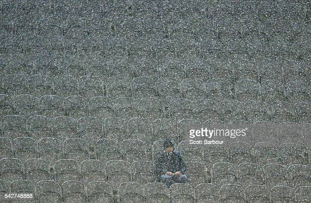 A lone Magpies supporter in the crowd looks on as it rains during the round 14 AFL match between the Collingwood Magpies and the Fremantle Dockers at...
