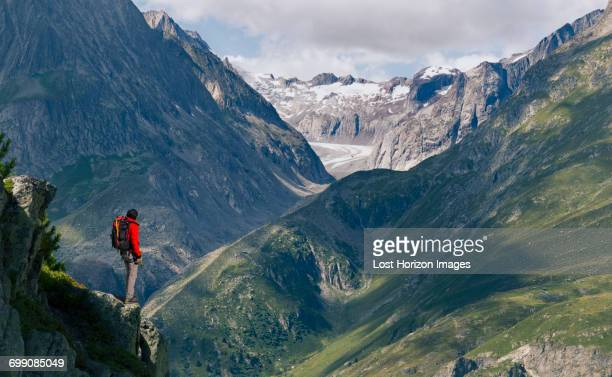 Lone male climber looking out from ridge, Aletsch Glacier, Canton Wallis, Switzerland