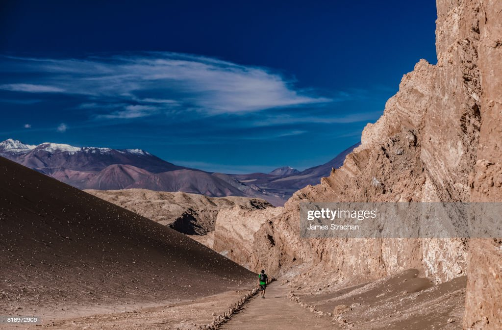 Lone male hiker trekking through the Valley of Moon, with snow-capped volcanic peaks in the background, near San Pedro de Atacama, Chile : Stock Photo