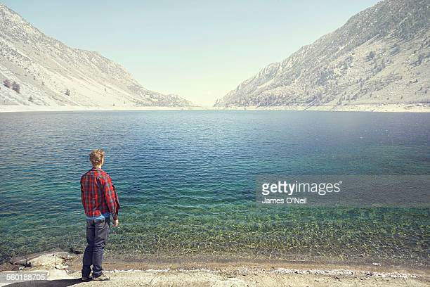 Lone male looking over mountain lake