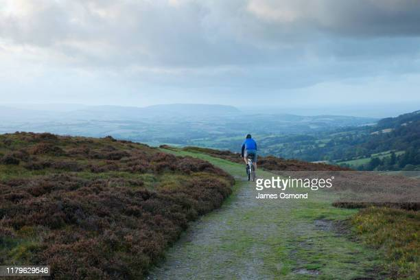 lone male mountain biking on an autumn evening. - headwear stock pictures, royalty-free photos & images