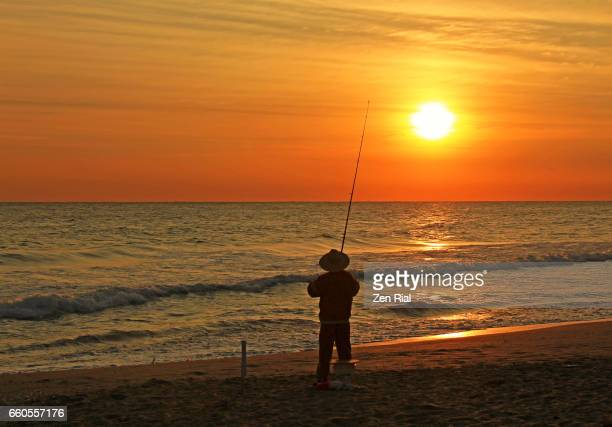 A lone man fishing on shore at sunrise facing the horizon across Atlantic ocean