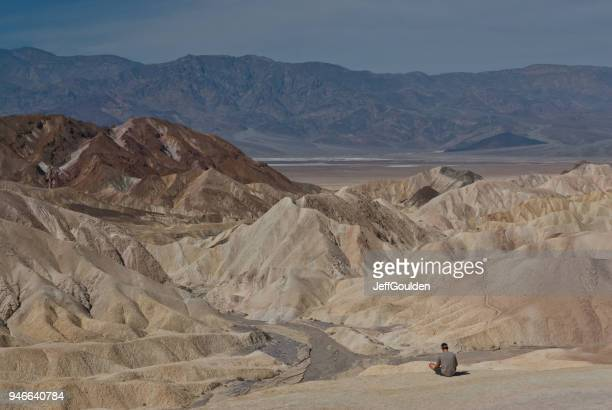 Young Man Sitting Near a Badlands Formation Above Badwater Basin