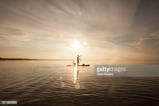lone man paddle boarding