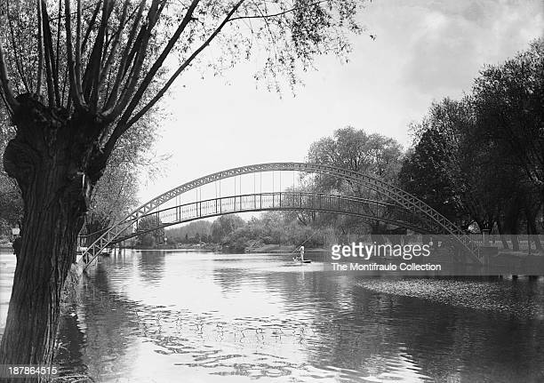 Lone man punting under an arched iron bridge on the River Ouse Bedford Bedfordshire England circa 1900