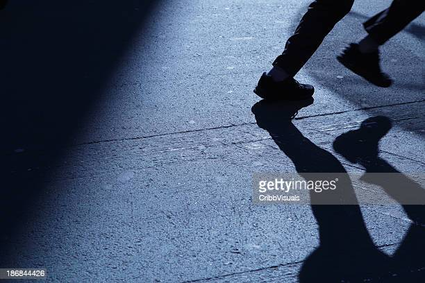 Lone man running away in blue night shadows