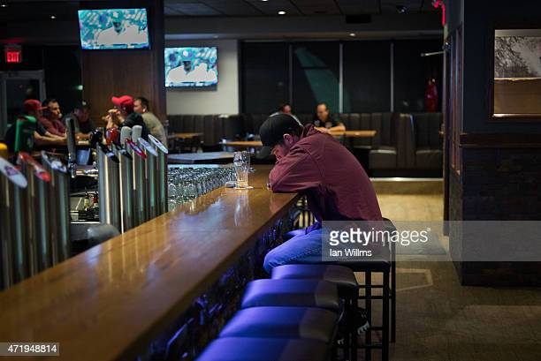A lone man sits in a bar in a on April 30th 2015 in a suburb of Fort McMurray Canada Fort McMurray is currently coping with an economic downturn as a...