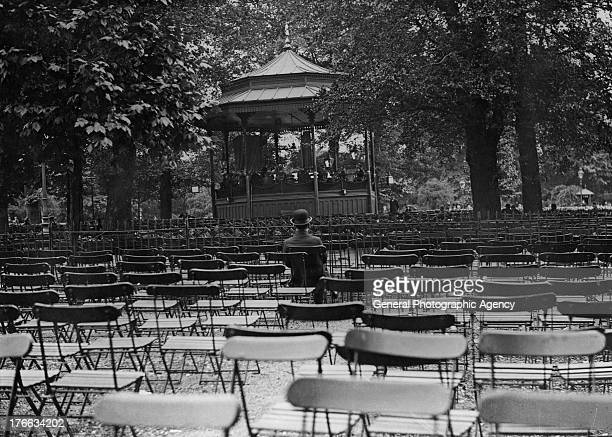 A lone man sitting amongst empty chairs listens to a band play at the bandstand in Hyde Park London circa 1935