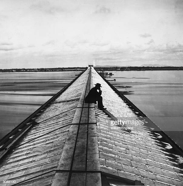 Lone man sitting on the Victoria Railway Bridge over the St Lawrence River in Montreal, during its construction. The single-track railway was fully...
