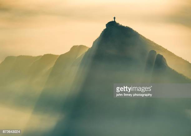 A Lone man stands on a jagged hill in misty conditions at sunrise, English Peak District. UK.