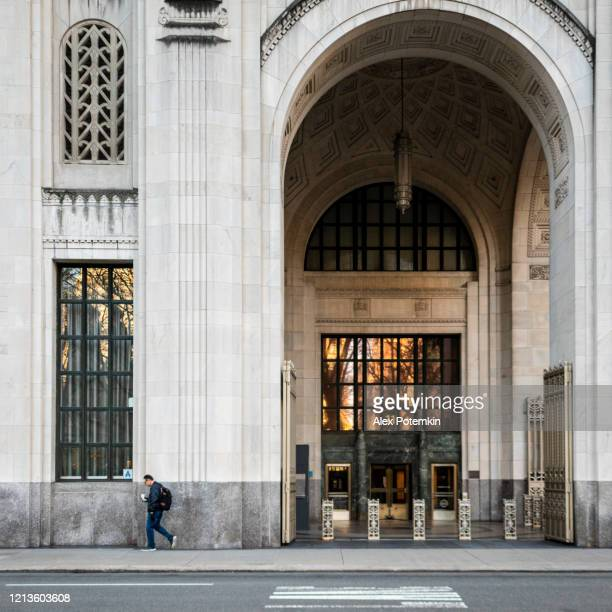 lone man walking in front of credit suisse office on madison avenue. - madison avenue stock pictures, royalty-free photos & images