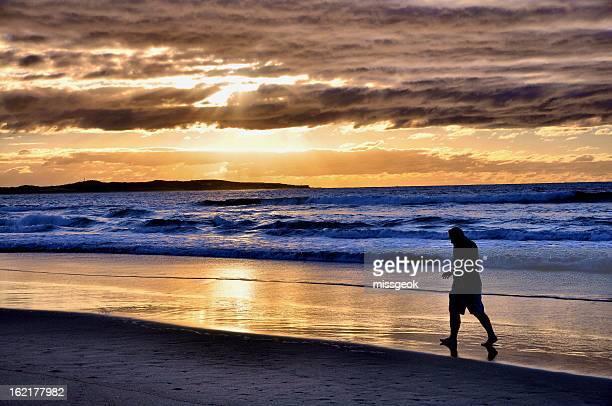 A lone man walking on Cronulla beach at sunrise