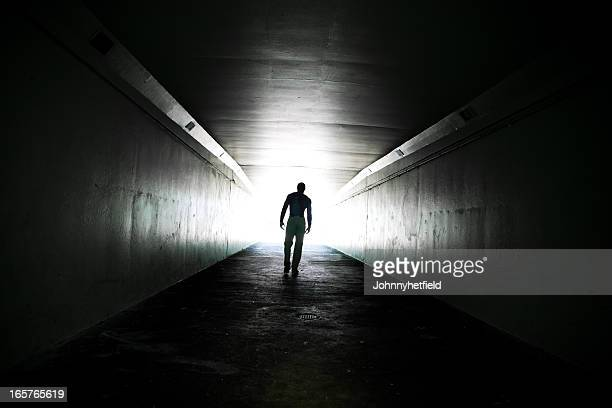 Lone man walking through tunnel