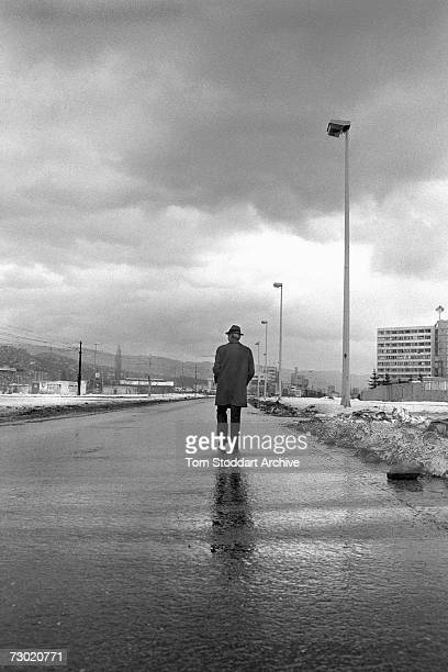 Lone man walks down Sniper Alley under rain filled storm clouds during a lull in the shelling. During the 47 months between the spring of 1992 and...