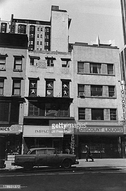 A lone man walks past closed shops on 9th Avenue Midtown West New York City 1982
