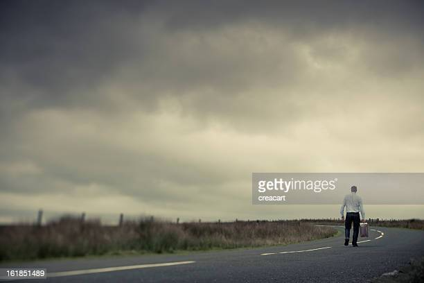 Lone Man with old suitcase on country road